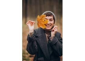 拿着叶子的秋天公园的少妇由面孔_12178054
