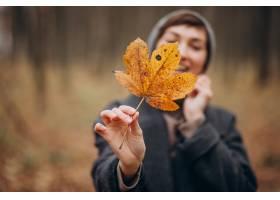 拿着叶子的秋天公园的少妇由面孔_12178056