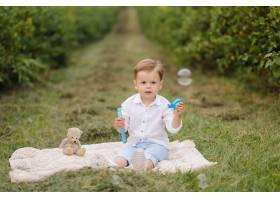 小男孩坐野餐格子花呢披肩在村庄庭院里_9409269