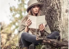帽子的女孩读一本书的在秋天森林里_9434539