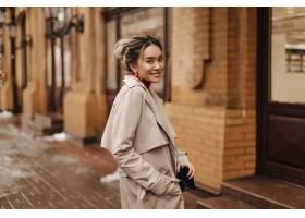 微笑的亚裔妇女在米黄秋天外套穿戴了拿着斜_12860452