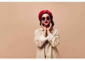 太阳镜和红色贝雷帽的可爱的夫人在米黄背景_13212089