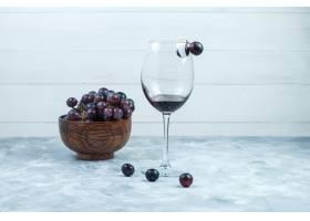 套一杯酒和黑葡萄在肮脏的灰色和木背景的黏_13786222