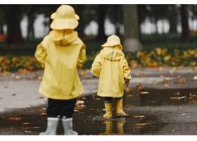 孩子们在秋天公园黄色雨衣的孩子人们在_11190793