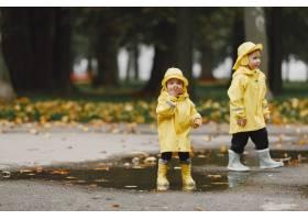 孩子们在秋天公园黄色雨衣的孩子人们在_11190798