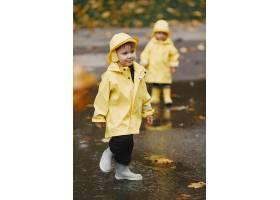 孩子们在秋天公园黄色雨衣的孩子人们在_11190808