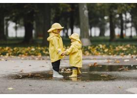 孩子们在秋天公园黄色雨衣的孩子人们在_11190812
