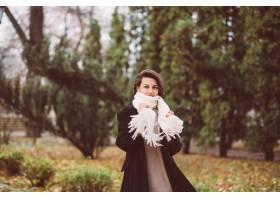 妇女室外画象在公园佩带的冬天黑外套和白色_13437437