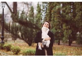 妇女室外画象在公园佩带的冬天黑外套和白色_13437439