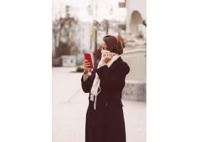 妇女室外画象黑冬天外套和白色围巾的在街道_13437422