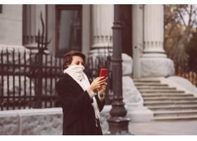 妇女室外画象黑冬天外套和白色围巾的在街道_13437423