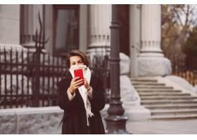 妇女室外画象黑冬天外套和白色围巾的在街道_13437425