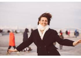 妇女画象冬天黑外套和白色围巾的在城市正方_13437443