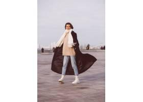 妇女画象冬天黑外套和白色围巾的在城市正方_13437451
