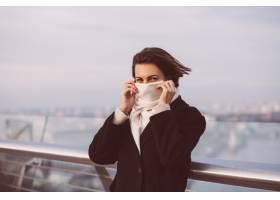 妇女画象冬天黑外套和白色围巾的在城市正方_13437454