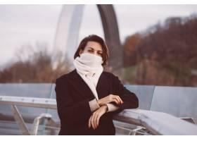 妇女画象冬天黑外套和白色围巾的在城市正方_13437458