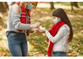 家庭在秋天公园冠状病毒主题有女儿的母_11799201