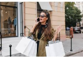 华丽的时尚asta妇女谈话在电话与朋友在购物_10786280