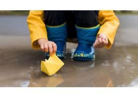 使用与纸小船特写镜头的小男孩_9365541
