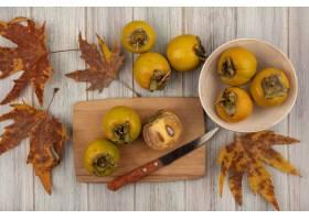 黄色柿子果子顶视图在一个碗的有叶子的与柿_13997441