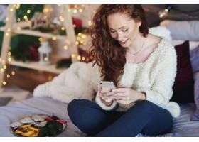 花费在床上的手机的女孩圣诞节时间_11755828