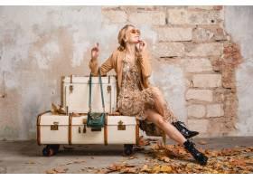米黄外套的可爱的时髦的白肤金发的妇女坐在_13869904