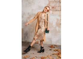 米黄外套的可爱的时髦的白肤金发的妇女走在_13869899