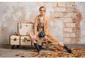 米黄外套的可爱的时髦的白肤金发的妇女走在_13870559