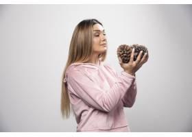 粉红色的运动衫的金发女士通过拿着橡树锥体_11726872