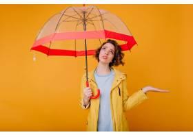 生气年轻女性模型室内画象在秋天雨衣的站_13601657