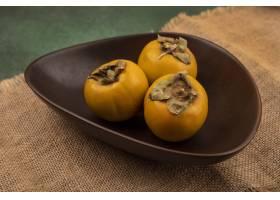 橙色柿子果子顶视图在一个碗的在一块袋子在_13664491
