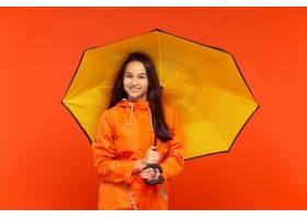 摆在秋天橙色夹克的演播室的愉快的微笑的女_11648636