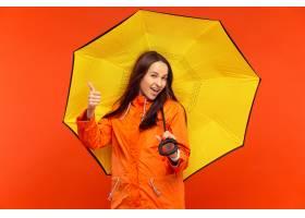 摆在秋天橙色夹克的演播室的愉快的微笑的女_12836946