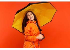 摆在秋天橙色夹克的演播室的愉快的微笑的女_13056318