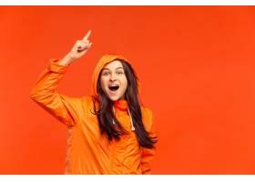 摆在秋天橙色夹克的演播室的愉快的微笑的女_14219810