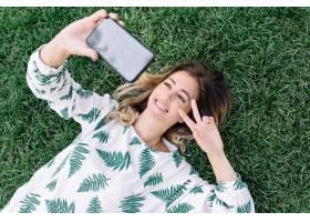 放置在草的俏丽的妇女在公园和做selfie在她_12965102