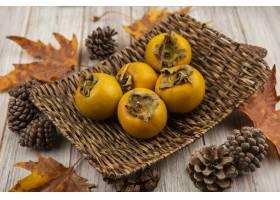 新鲜的柿子果子顶视图在一个柳条盘子的与叶_13996554