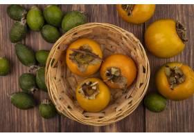 新鲜的柿子果子顶视图在一个桶的与在木墙壁_13663326