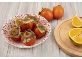 新鲜的柿子顶视图在一个碗的有在一个木厨房_13666190