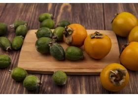 新鲜的橙色柿子果子顶视图与feijoas的在木_13806977