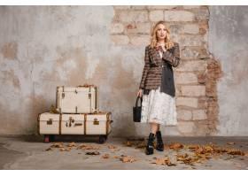 方格的夹克的可爱的时髦的白肤金发的妇女走_13869811