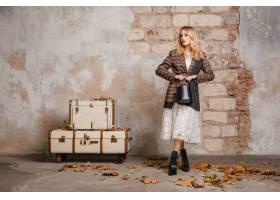 方格的夹克的可爱的时髦的白肤金发的妇女走_13869814