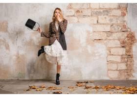 方格的夹克的可爱的时髦的白肤金发的妇女走_13869825