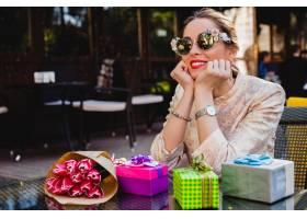 时尚太阳镜的年轻时髦的美丽的妇女坐在与礼_9644058