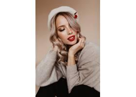 时髦贝雷帽的沉思妇女坐棕色墙壁_12305327
