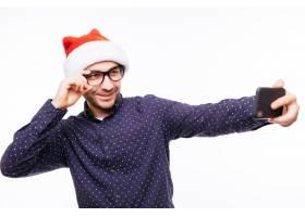 年轻愉快的情感人佩带的圣诞节圣诞老人帽子_15181094