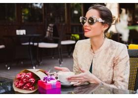 年轻时髦的妇女坐在咖啡馆的时尚太阳镜_9644077