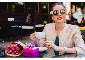 年轻时髦的妇女坐在咖啡馆的时尚太阳镜_9644079
