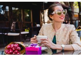 年轻时髦的妇女坐在咖啡馆的时尚太阳镜_9644083