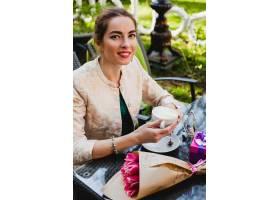 年轻时髦的妇女时尚太阳镜坐在咖啡馆_9644087